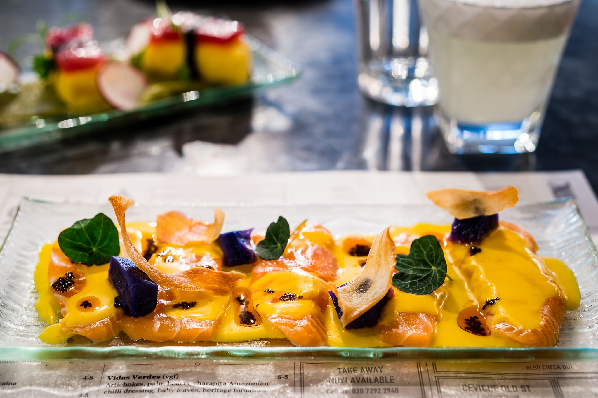 Tiradito Apasionado: Sustainable salmon, passion fruit tiger's milk, purple potato, chia seeds, cassava crisps, nasturtium leaves