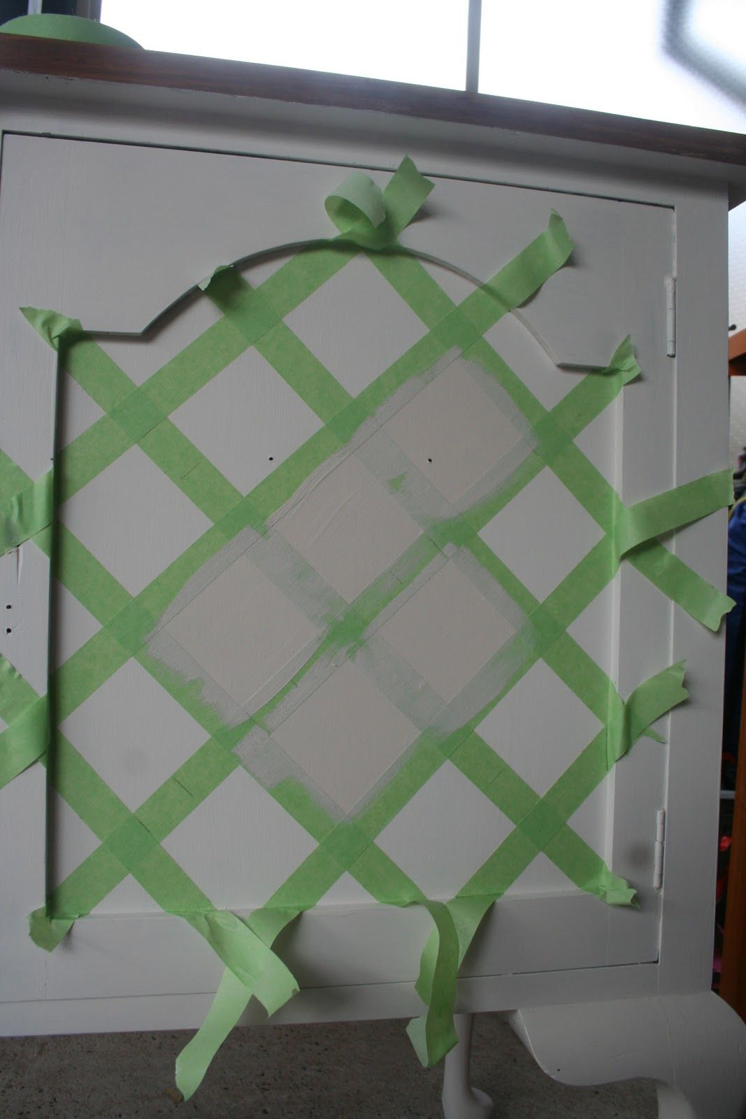 Painters tape to create trellis pattern, could be tone on tone, or color over woodtone, and then distress (maybe the sides of the buffet).