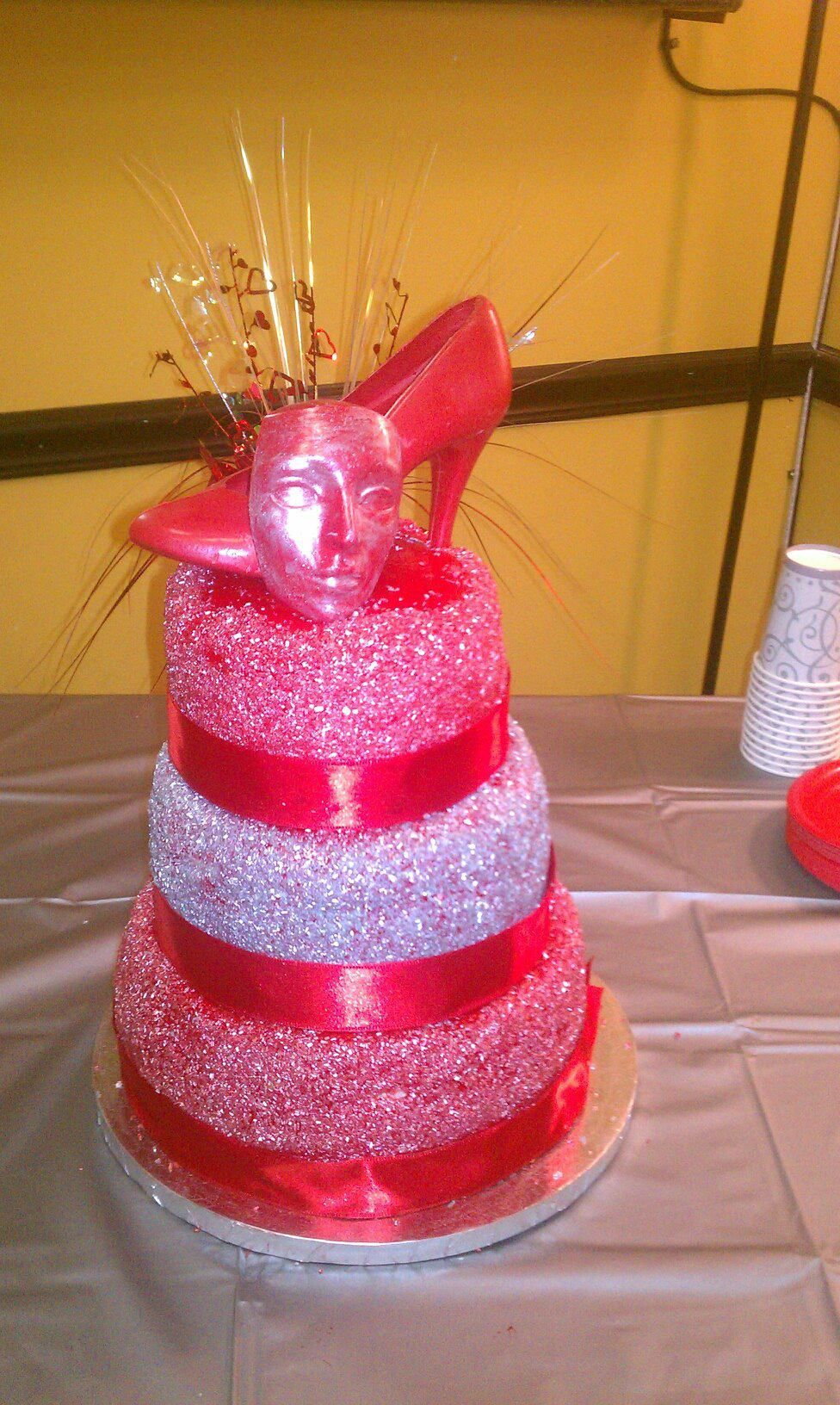 Red and silver tiered wedding cake topped with a red hell and mask