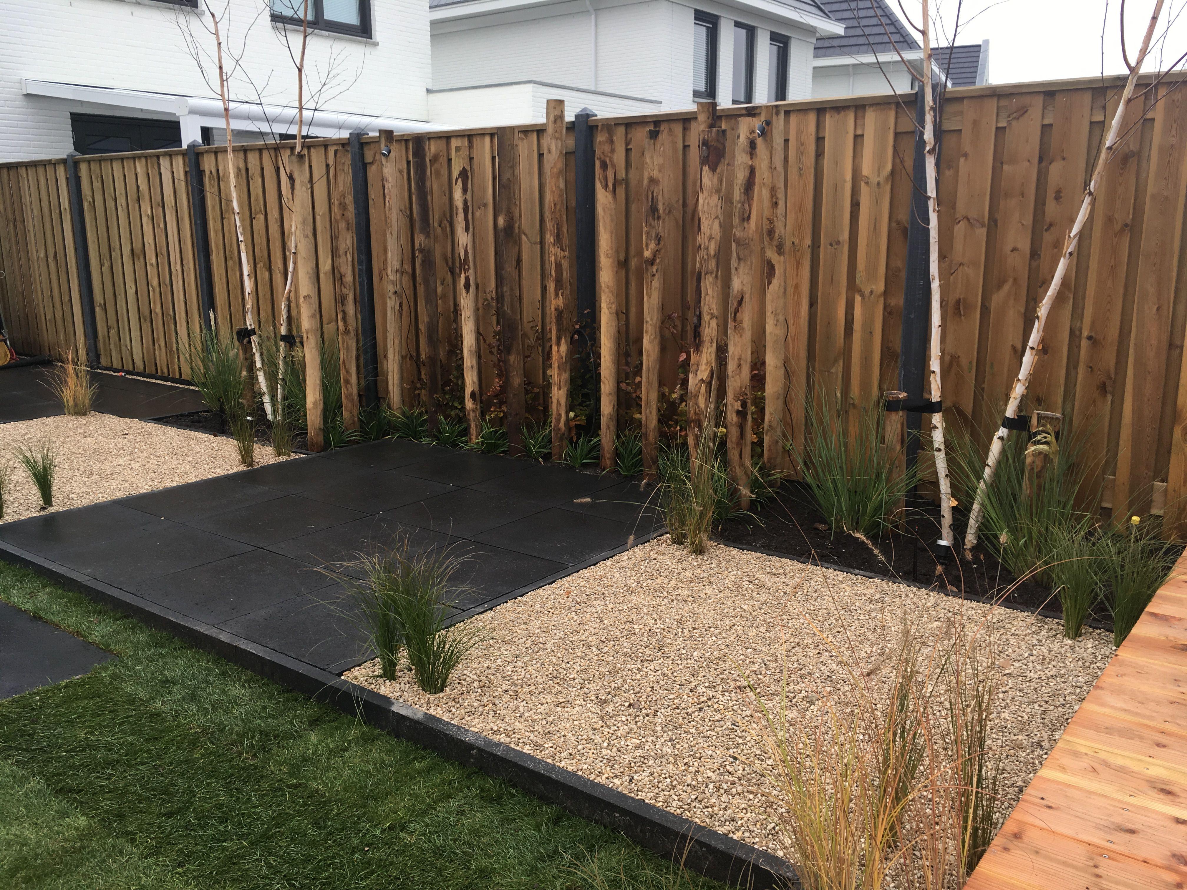 Welp Terras midden in de tuin afgeschermd met kastanje houten palen en AD-19