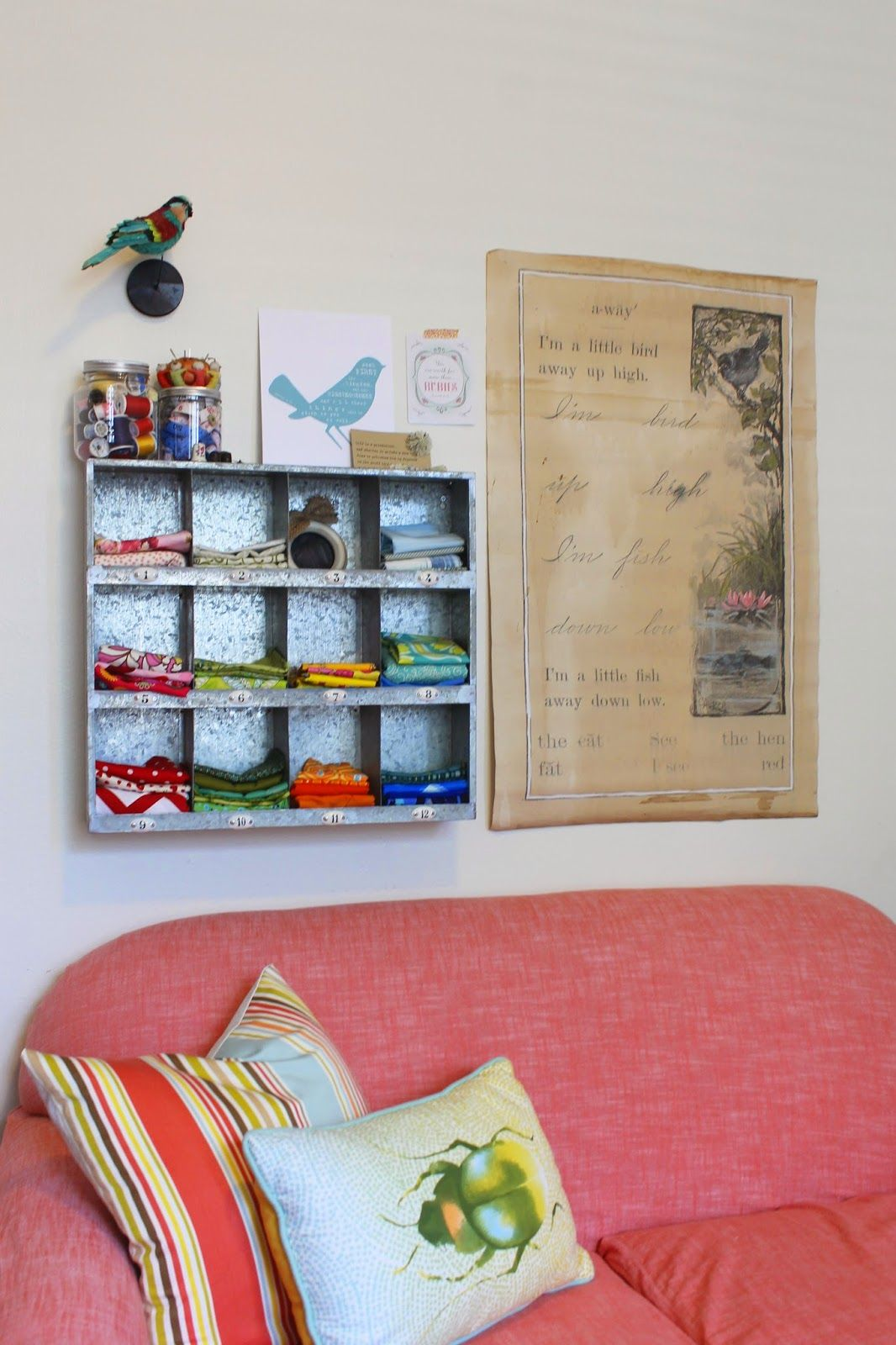Great craft room space, with the perfect seating area. Small love seat gets a new life with a duvet cover, made into a slip cover. Fun pop of coral, mixed with different colors, and patterns. Anything goes here. Galvanized metal shelf, holds bits of fabir. And sewing supplies in jars. Painted antique paper, and art hangs over couch. Lots of open shelving, are perfect for displaying a collection of craft items, or collectables.  Simple and cheap ikea shelving!   Theraggedwren.blogspot.com