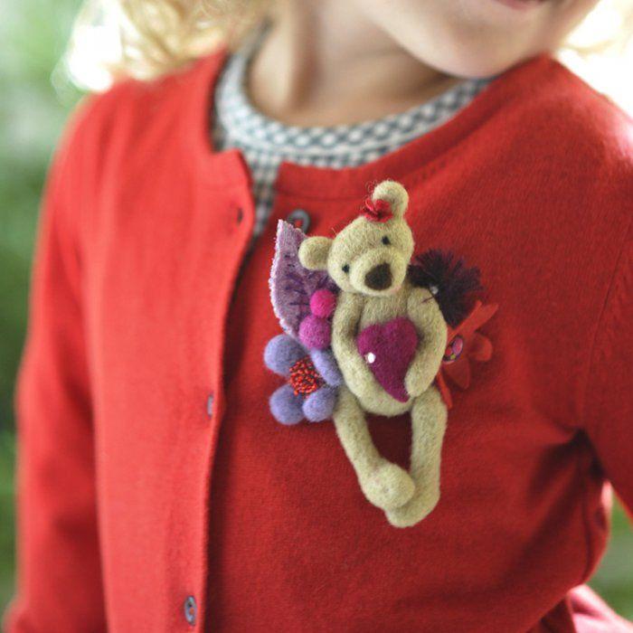 Explications de la broche en laine feutrée petite oursonne avec un cœur.