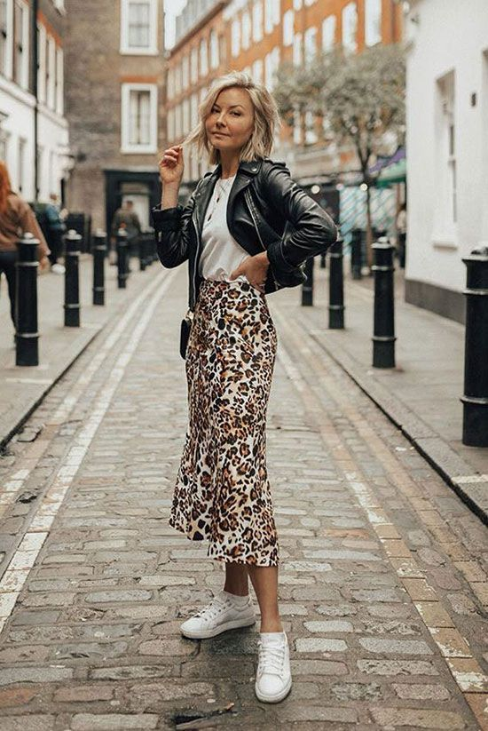 @laurie_ferraro wearing a black leather jacket, a white t-shirt, a leopard skirt and white sneakers. Leopard skirt outfits, leopard midi skirt outfits, satin skirt outfits, spring outfits, casual outfits, street style, fashion trends 2019, spring fashion trends 2019, casual style, #fbloggerstyle #casualstyle #streetstyle