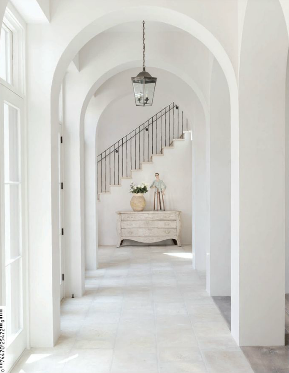 Gorgeous arched doorways, white stone floors and iron stair railings ...