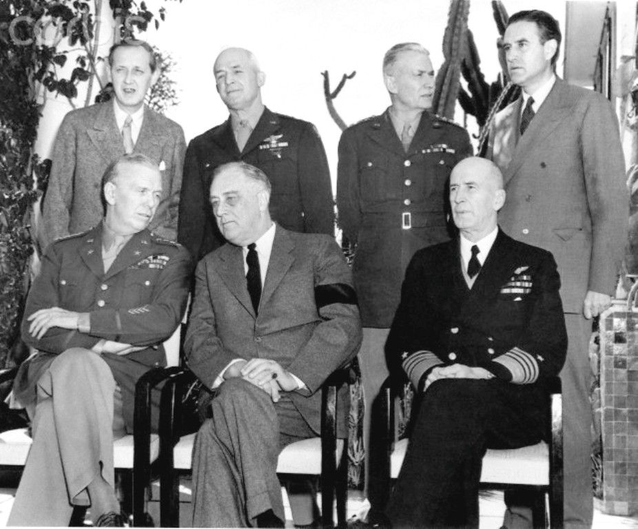 The U.S. leaders sit in the President's villa in Casablanca for a meeting with the British. Left to right, seated: Chief of Staff General George C. Marshall, President Franklin D. Roosevelt, Admiral E.J. King. Rear: Harry Hopkins, U.S. Army Lieutenant General Brehon Somervell, an Army Commanding General, and Averell Harriman.