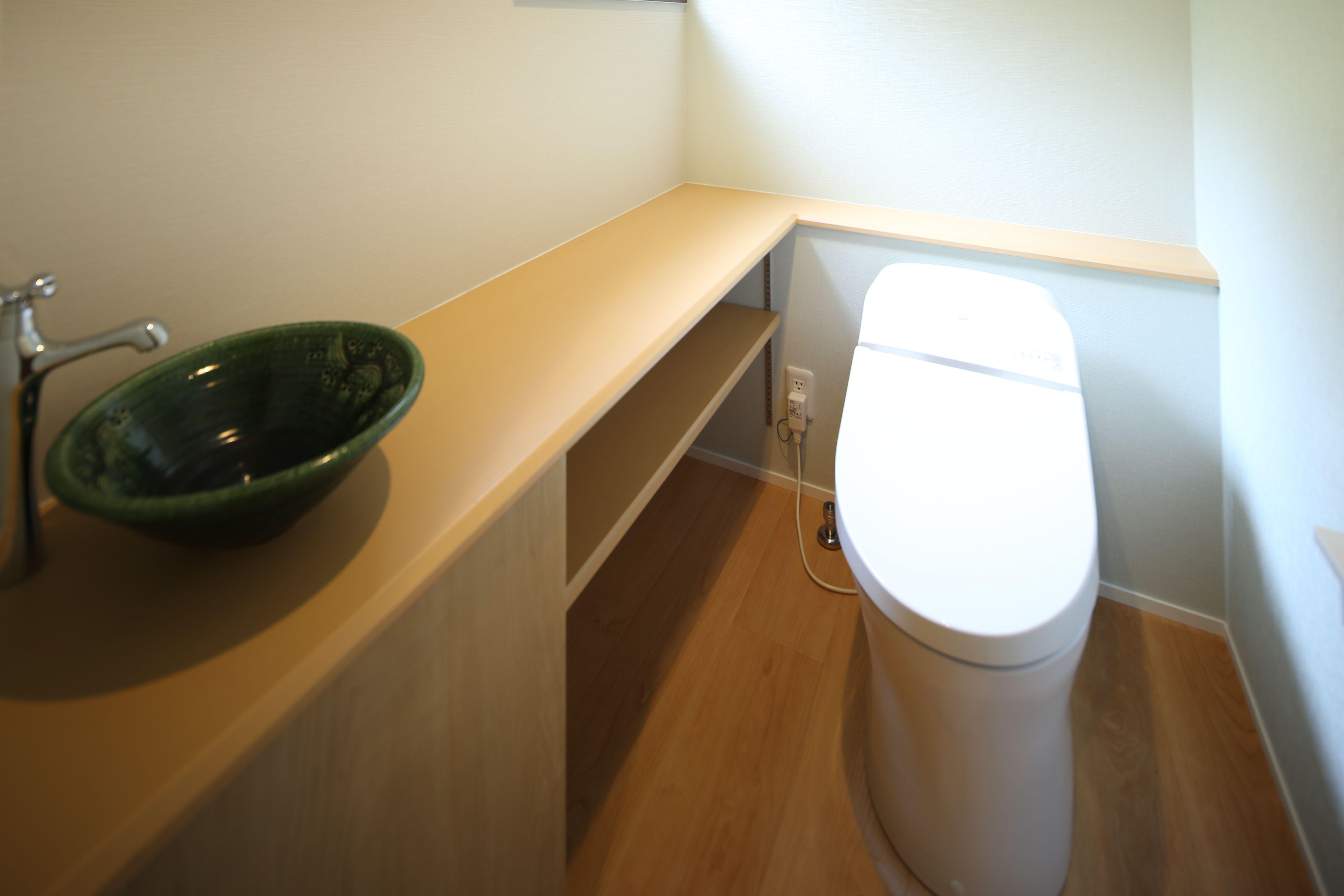 Totoさんのタンクレストイレ 造作の収納棚の上に手洗い陶器と水栓 を