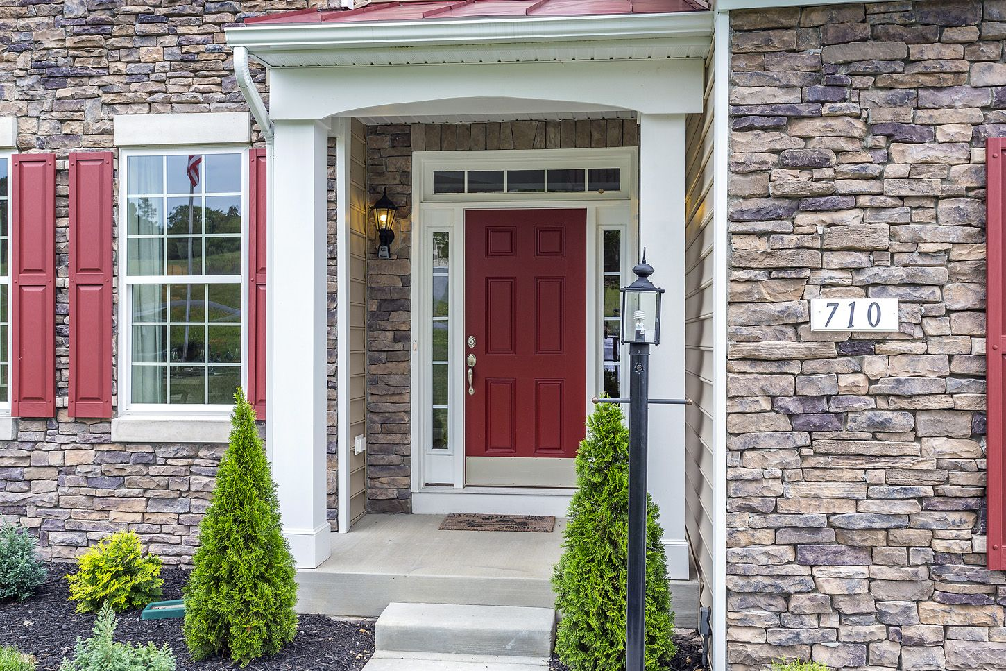 Red Doors Stone : Beautiful model home with stone siding red shutters
