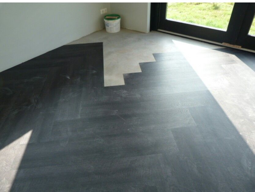 Zwarte pvc vloer in visgraat leggen nieuw huis
