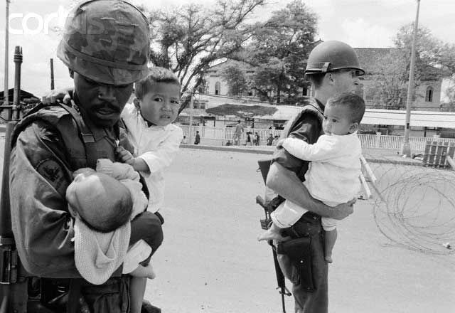 Vietnam War - US soldiers carry Vietnamese children to safety. The look on the face