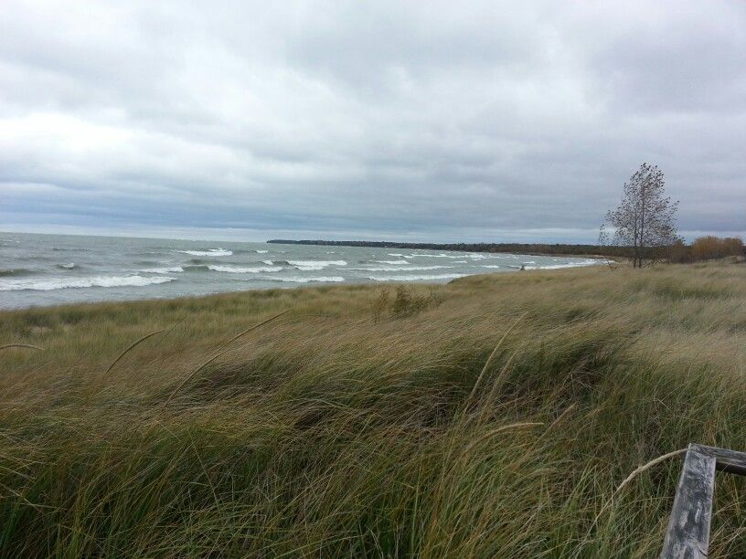 Waves crash against the shore on a dreary day at the dunes of Port Crescent State Park in Michigan.
