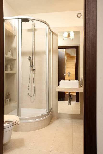 ŁAZIENKA: Funkcjonalny projekt. Wnętrze zostało bardzo funkcjonalnie zaprojektowane. Dzięki zastąpieniu wanny kabiną prysznicową wygospodarowano miejsce na pojemne schowki. Aby liczne wnęki nie wprowadzały optycznego niepokoju, wyłożono je takimi samymi płytkami co ściany i podłogi.
