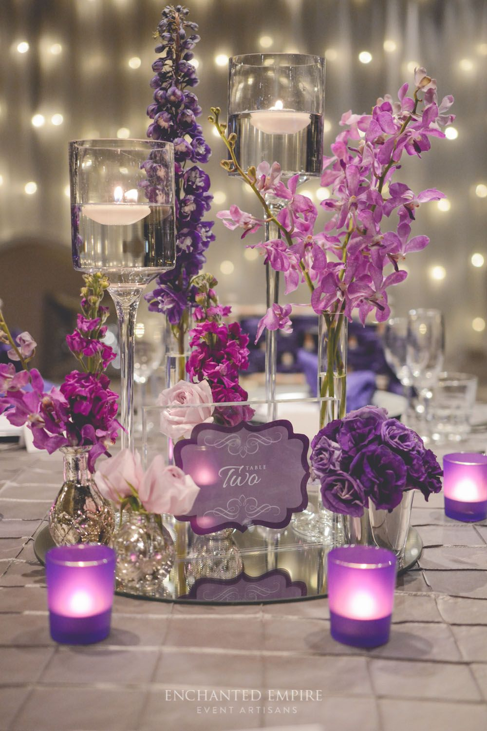 With fairy light walls, the light from this wedding illuminated an assortment of purple florals on exquisite silver pintuck tablecloths. Silver charger plates, ornate napkin rings and purple frosted tealights were accentuated by custom designed stationery. Menus, table numbers and place cards were adorned with a custom purple wax seal. The intimate and romantic style our couple strived for was finished with Limewash Tiffany chairs dressed in crushed taffeta sashes…