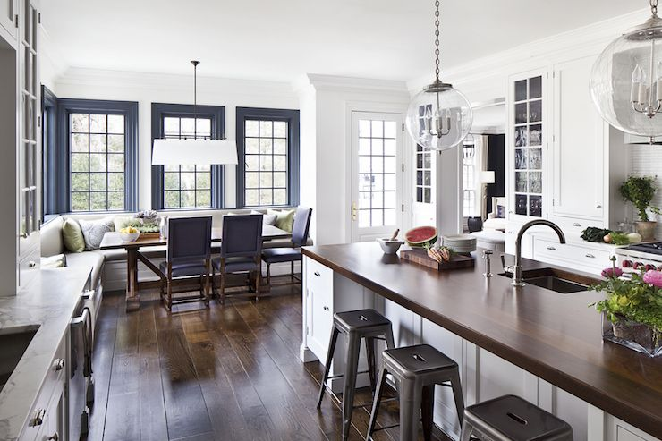 Amazing kitchen features etched glass pendants over long island