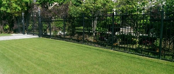 A Tall Wrought Iron Fence And Front Driveway Security Gate Provide A  Barrier, But Still