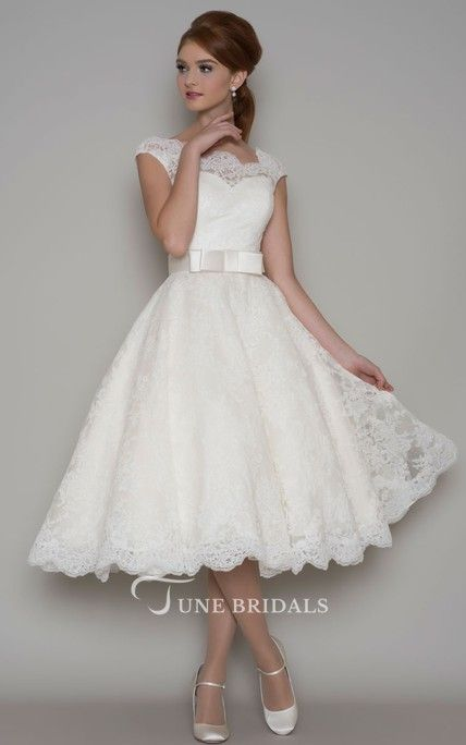 Vintage inspired tea length wedding dress shown with ivory corded lace over pale pink trimmed with a narrow satin bow belt.