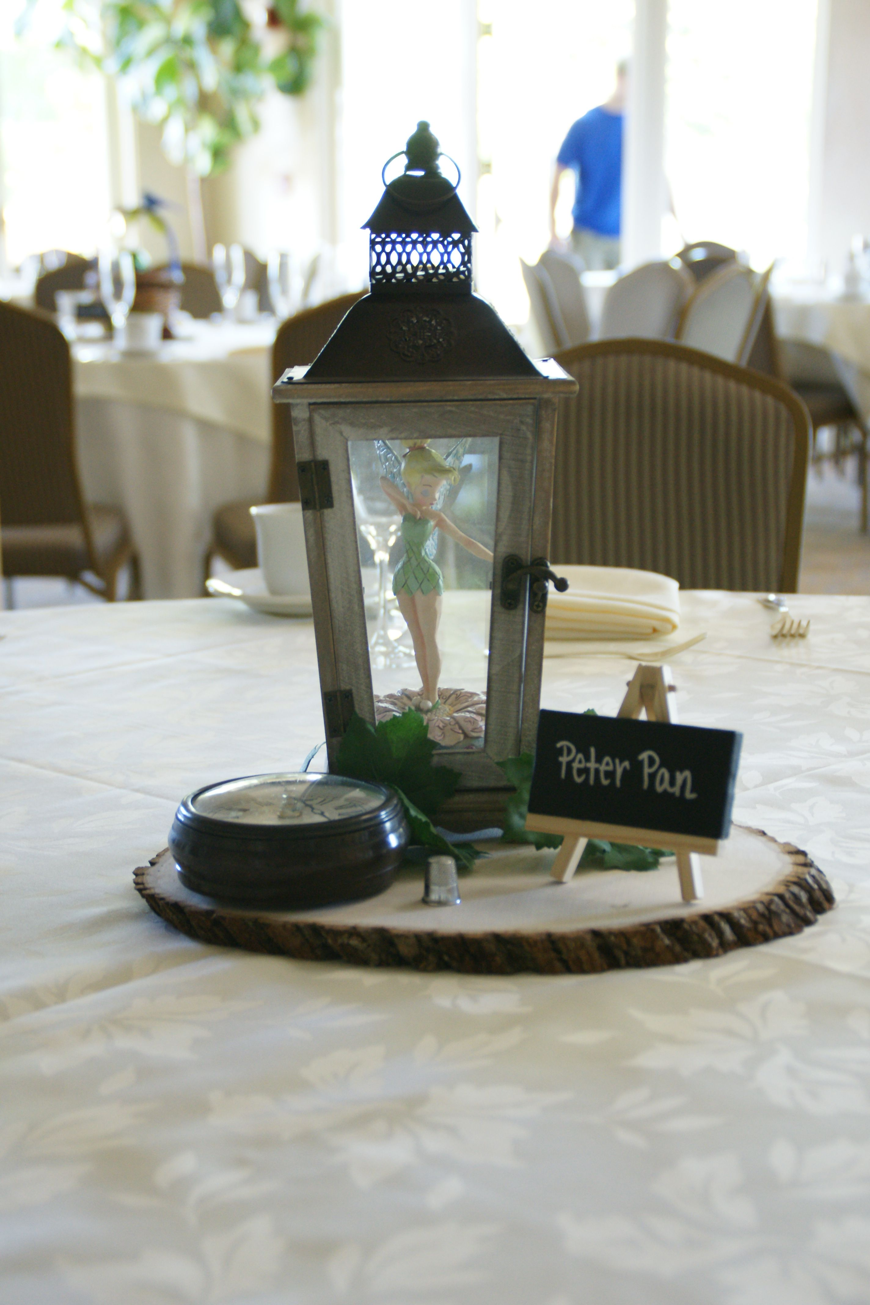 PETER PAN CENTERPIECE: Bought the lantern, and wooden base at an Arts & Crafts store. Bought the time watch and thimble at a thrift store. Put a Tinkerbell into the lantern and there you go! A trapped Tinkerbell!
