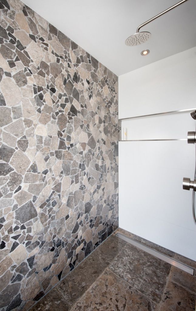 Badkamer ingericht met natuursteen. Op de wand zit palladiana en ...