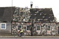 Cyklista jazdí okolo domu, ktorého exteriér je zdobený starými hrncami a panvicami v Zagare, 130 km západne od Vilniusu 29. októbra 2016.