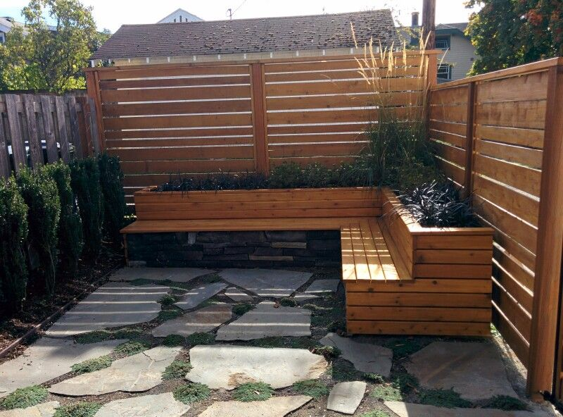Treated and stained wood seat wall with planter box.