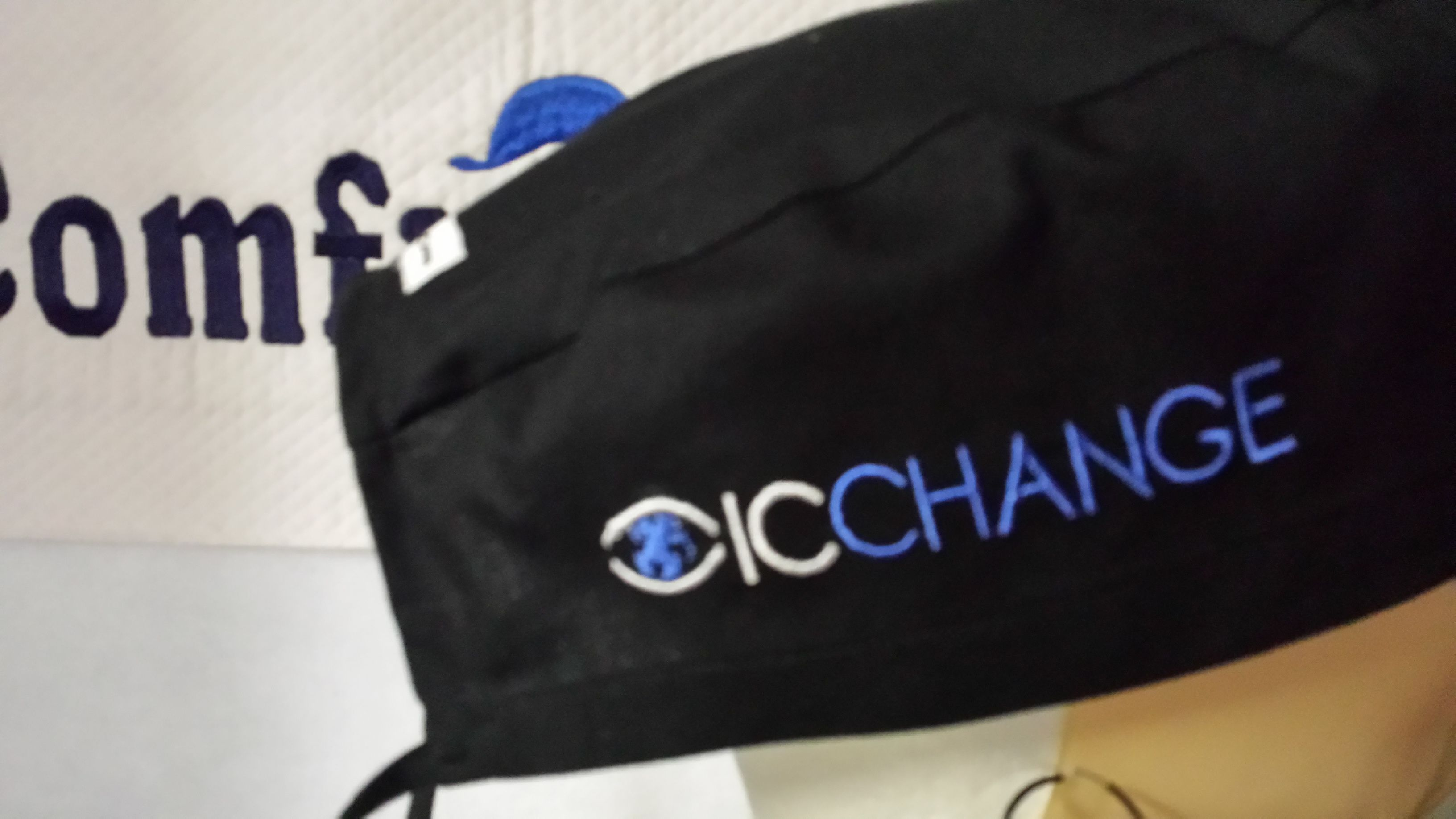 ICChange company logo embroidered on the side of a male scrub cap.