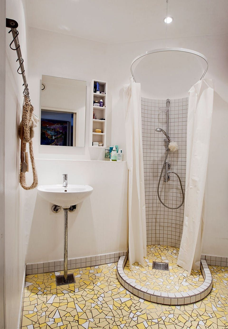 Retro-inspired bathroom with selfmade yellow mosaic floor and a shower cabin built in the old fire stove's place.