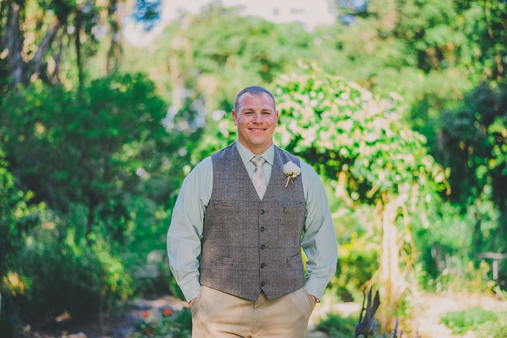 handsome groom wearing wool vest, mint green shirt with khaki pants at Cross Creek Ranch