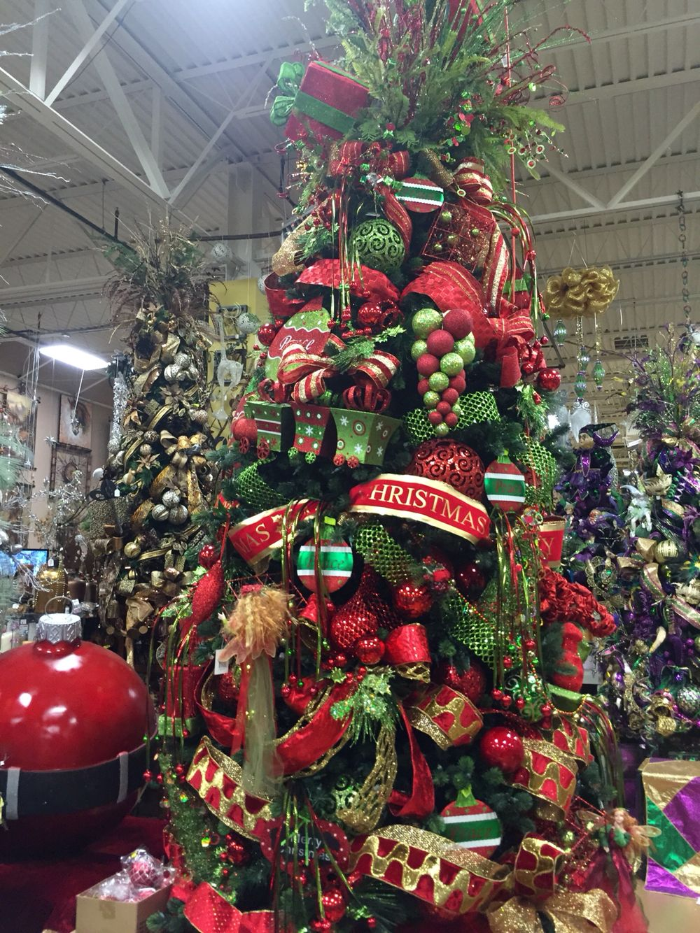 red and green whimsical christmas tree designed by arcadia floral and home dcor