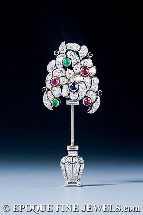 An Art Deco onyx, diamond, ruby, sapphire and emerald jabot pin, mounted in platinum and gold. The brooch is set with baguette cut, old European cut and single cut diamonds. The rubies, sapphires and emeralds and onyx are cabochon cut. France, ca. 1925<3<3<3