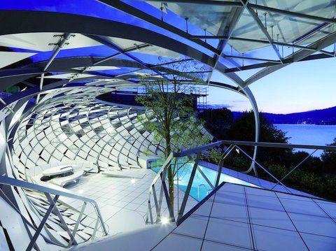 Cerca giratória para luz natural. Com sede em Viena, a equipe de arquitetos e Salli Heri projetou uma estrutura geométrica não convencional. Construído em torno de uma piscina, as curvas proporcionam privacidade e modernidade, e ao mesmo tempo, permite que a área seja bem ventilada e espaçosa. A estrutura é feita de tiras de metal na diagonal em formas de diamante que podem girar, permitindo a abundância de luz natural. Eles misturaram para completar os elementos funcionais no design.
