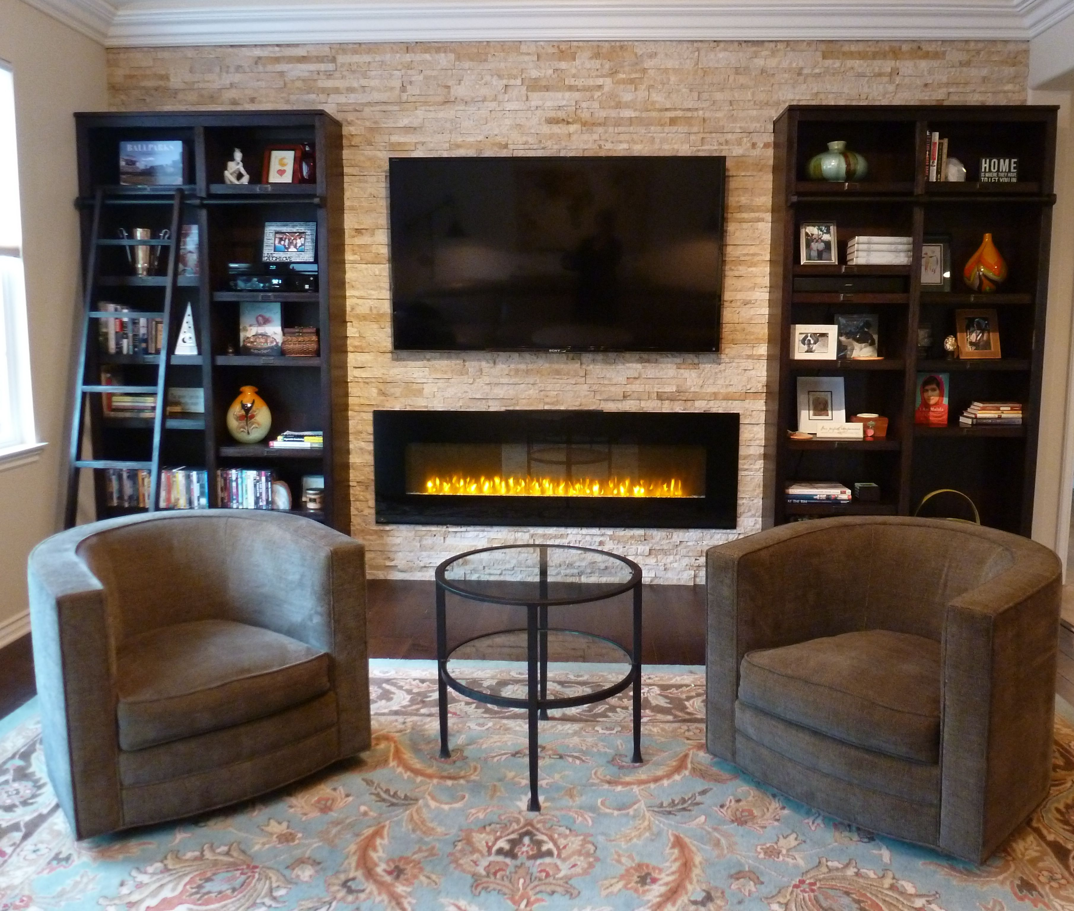 focal point wall using stacked stone bookshelves tv and a ribbon