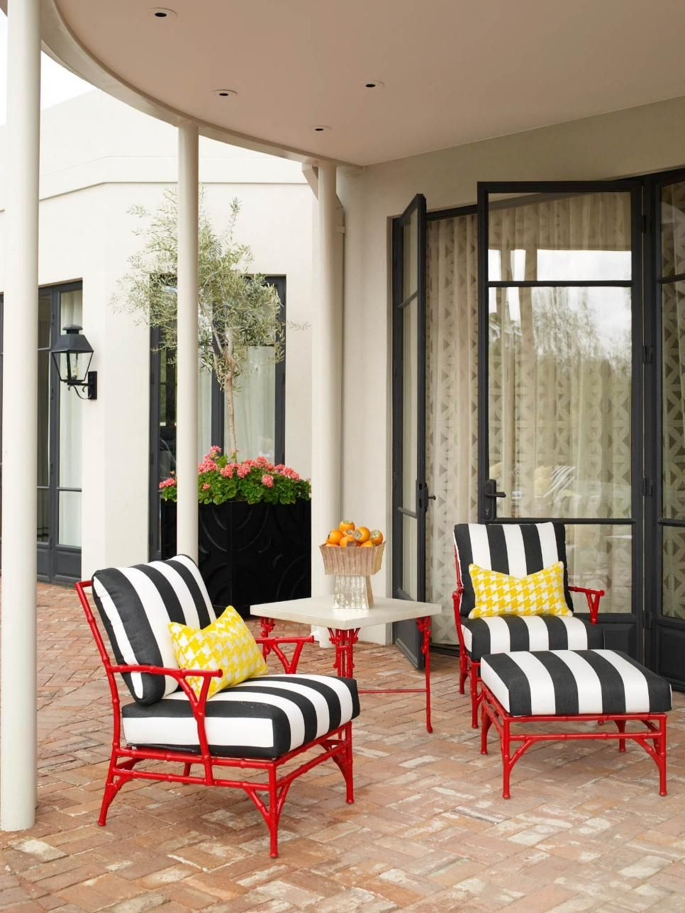 Art deco style bamboo furniture is given a modern update with a coat of glossy red paint black and white striped cushions and a fun yellow houndstooth