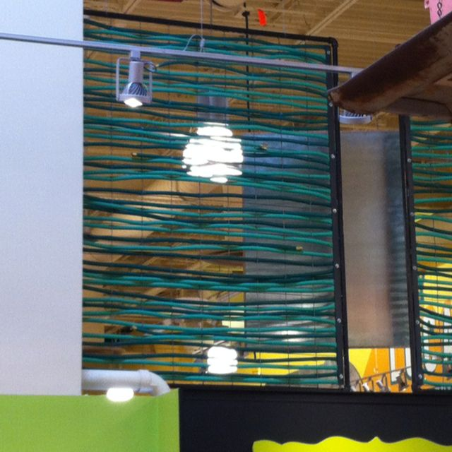 Whole Foods, South, in Austin, Texas uses garden hoses threaded through square-wire fencing as decor.  Love it!