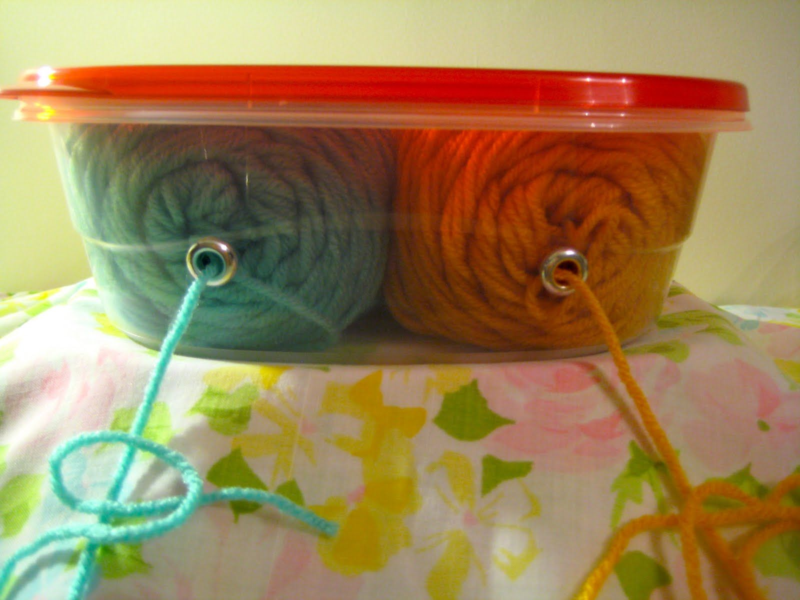 Great idea for keeping yarn tidy for multi-colored projects - punch/drill holes in one side of plastic container large enough to fit two skeins, grommet holes, thread yarn through, and work stays neat.  Genius diy from Chatterbox Jenn