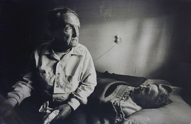 Man clutching eviction notice as he sits by his dying wife.                      Image by photojournalist, Joel Davis