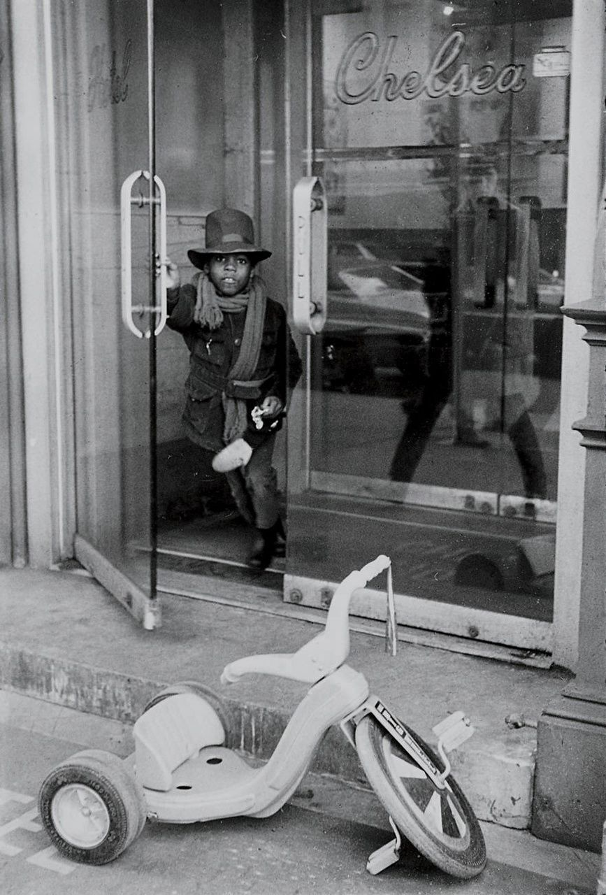 Boy exiting the Chelsea Hotel and headed to his Big Wheel (1971)