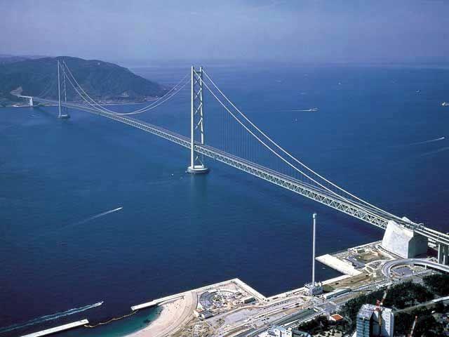 Puente de Akashi Kaikyō (Japón).  se encuentra la pequeña isla Awaji entre Honshu ja Shikoku. se comenzó la construccion en Mayo de 1988, y el período de construcción duró diez años. De su tipo es un puente colgante de tres tramos, dos colgantes articulados con armaduras de acero reforzado, vigas para la estructura del tablero.  Largo: 4 Km.
