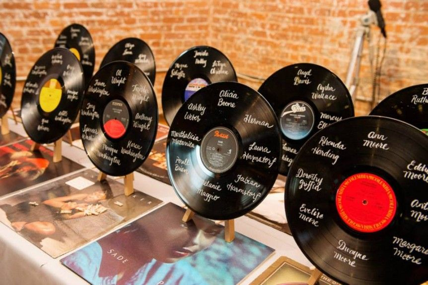 The couple noted the guests table seating chart with retro vinyl records.