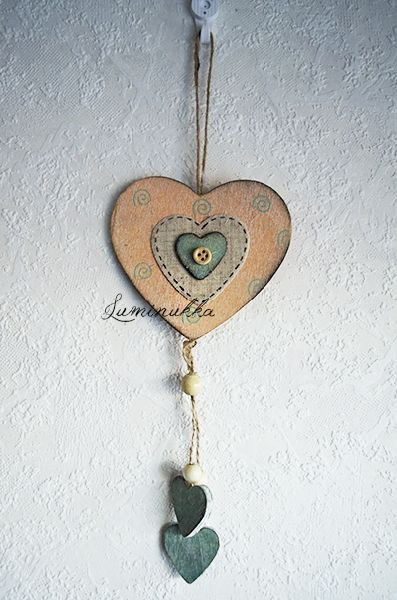 Persikansävyinen, rustiikkisen puinen sydän spiraalikuvioilla ja veikeällä nappisydämellä, Kokonaispituus 30 cm. // Rustic, peachy pink heart-shaped decoration for example to the nursery. Total length 30 cm.