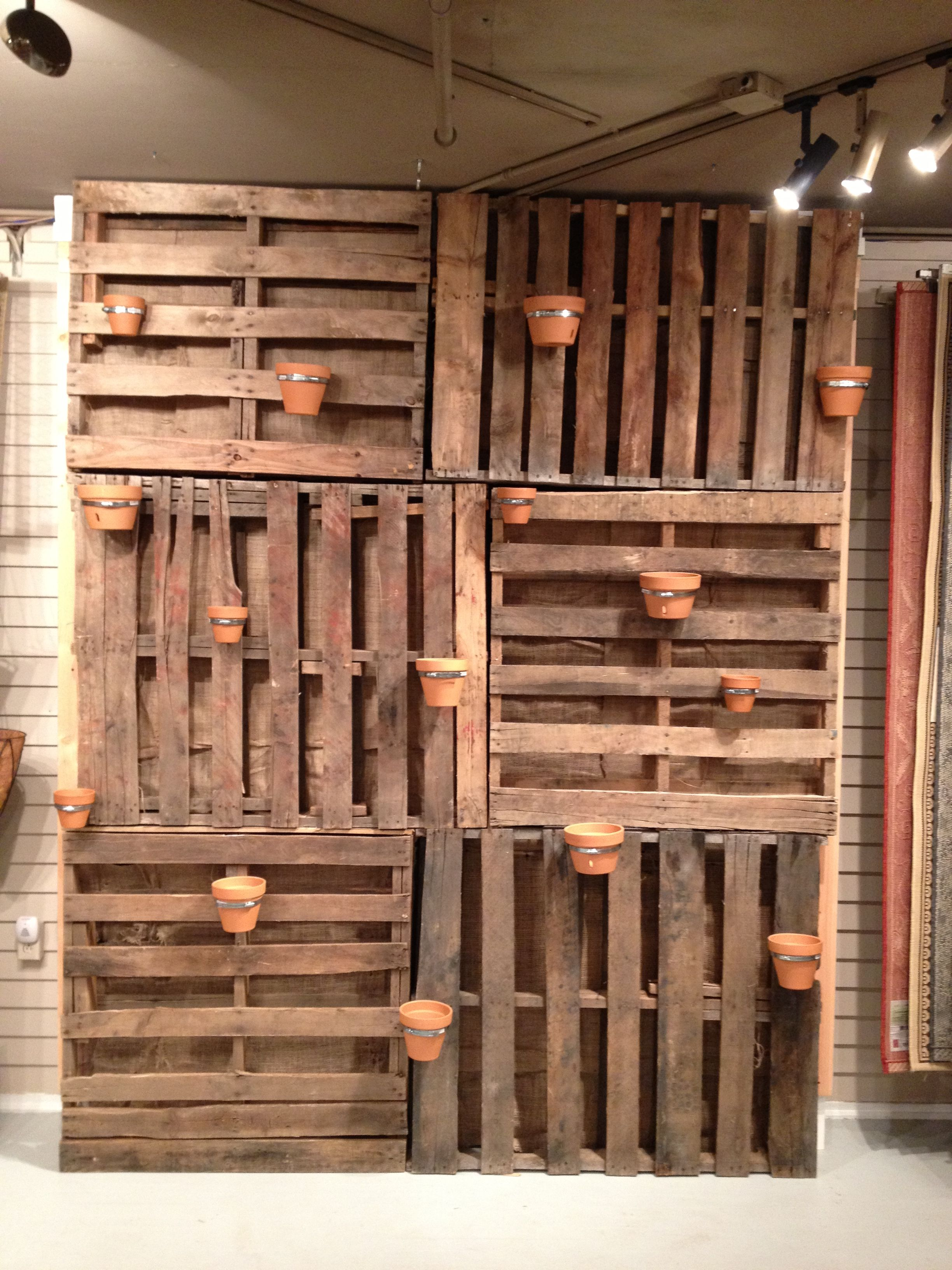 Garden wall made from pallets added air duct straps to for Wood pallet privacy walls