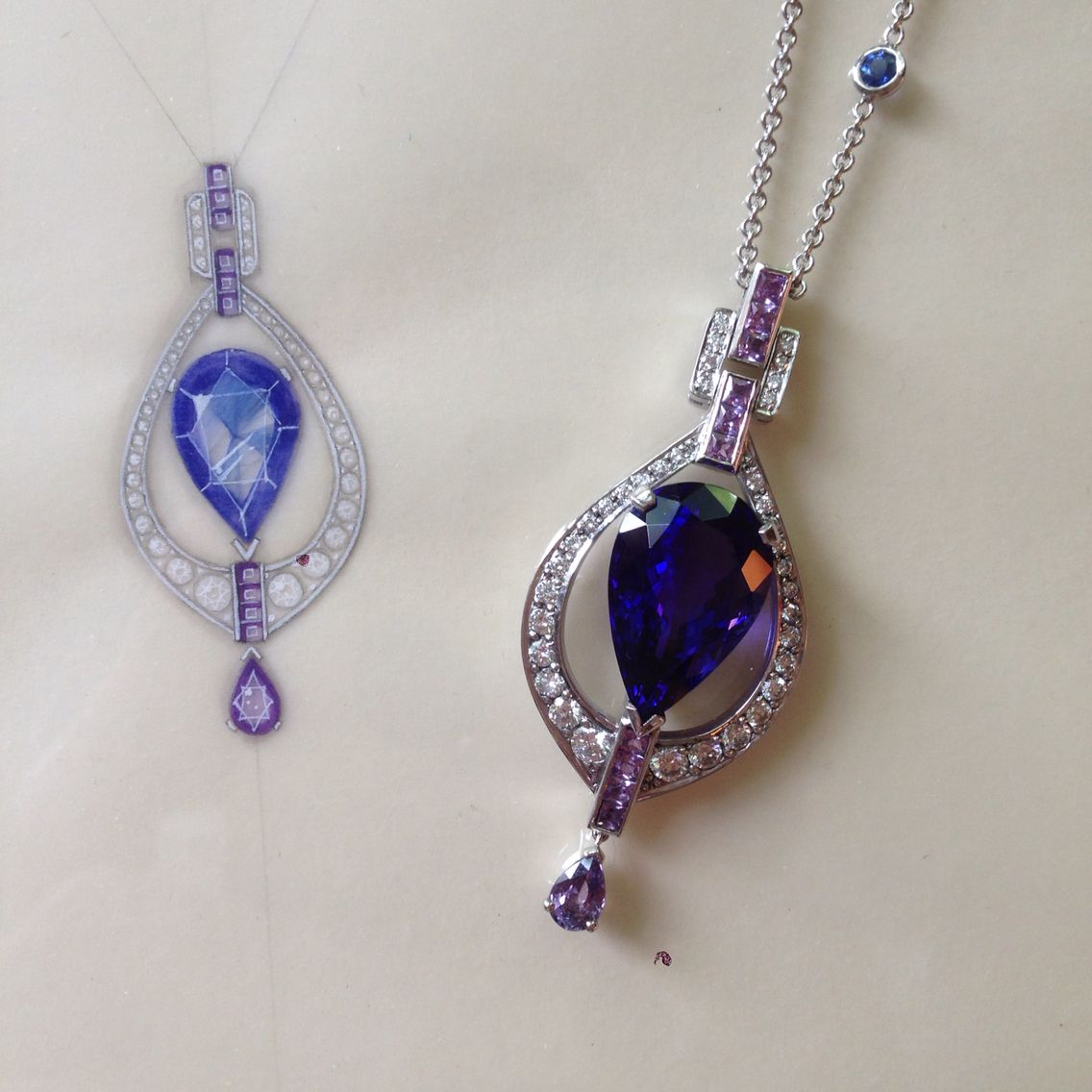 A tanzanite and violet sapphire Art Deco style pendant pictured next to the working drawing.