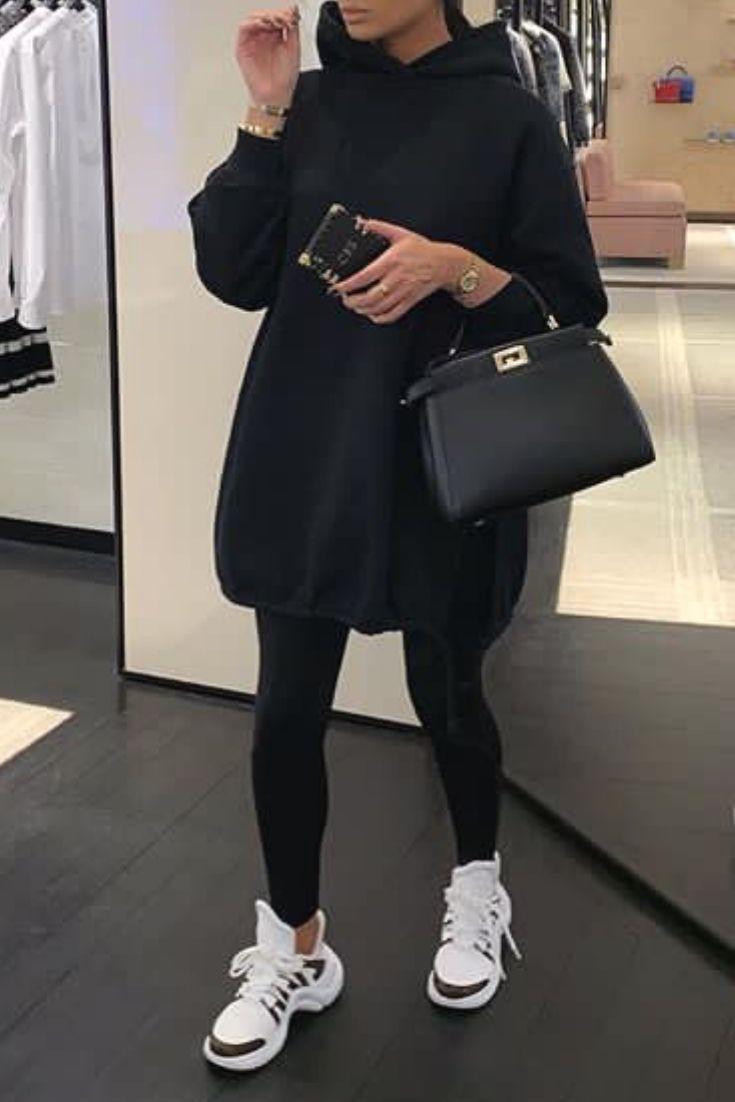 Lässige und bequeme Frau mit schwarzen Leggings einem langen schwarzen Sweatshirt und Turnsch…