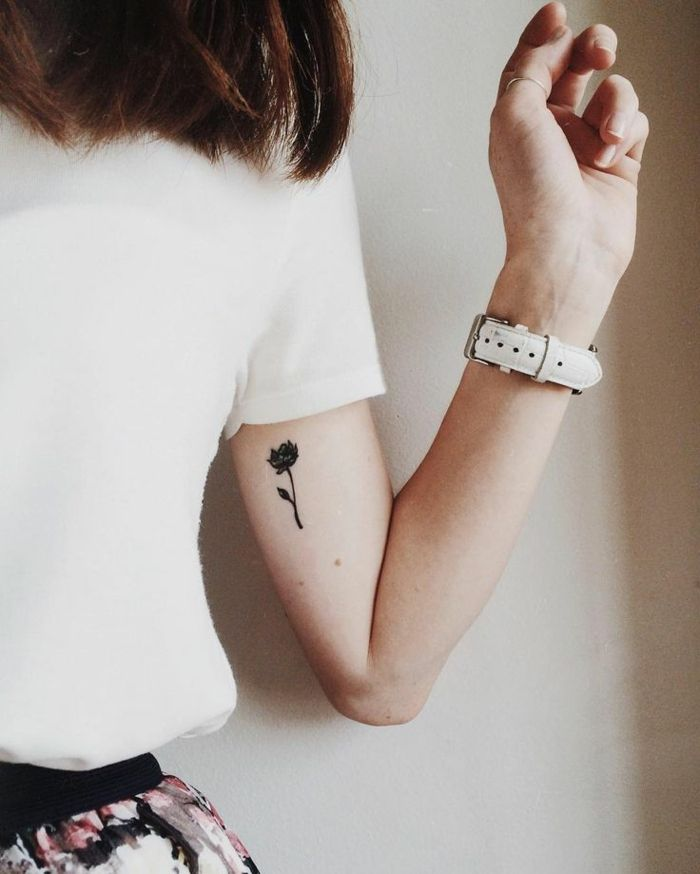 auburn-haired woman, wearing white t-short, a tiny black tattoo of a flower on her upper hand