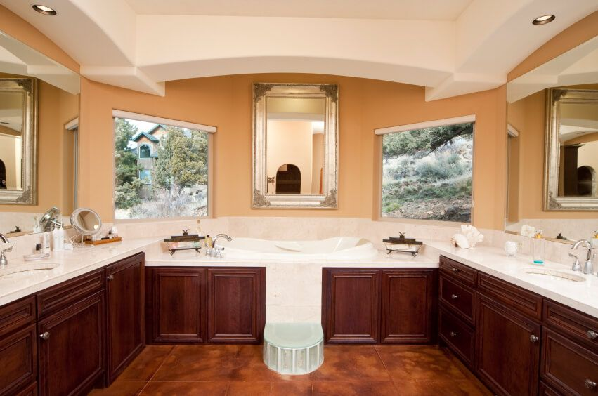 This outrageously luxurious bathroom features a separate double vanity for optimal room for daily preparations. The sink areas face each other, and reveal plenty of counter space for all the required toiletries. A unique bathtub sits high in its encasement, and a built in frosted glass step allows for ease of access. Large windows reveal relaxing views of the outdoor area, while mirrors reflect their surroundings, opening up the space further.