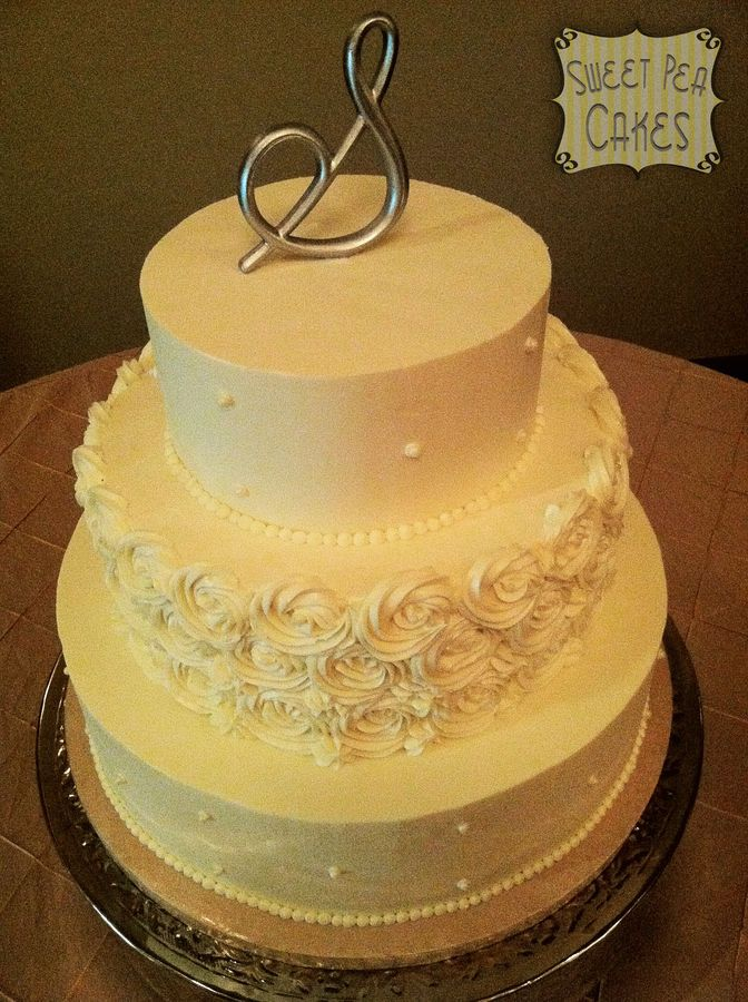 Three tier buttercream wedding cake with rosettes and pearls. The ...