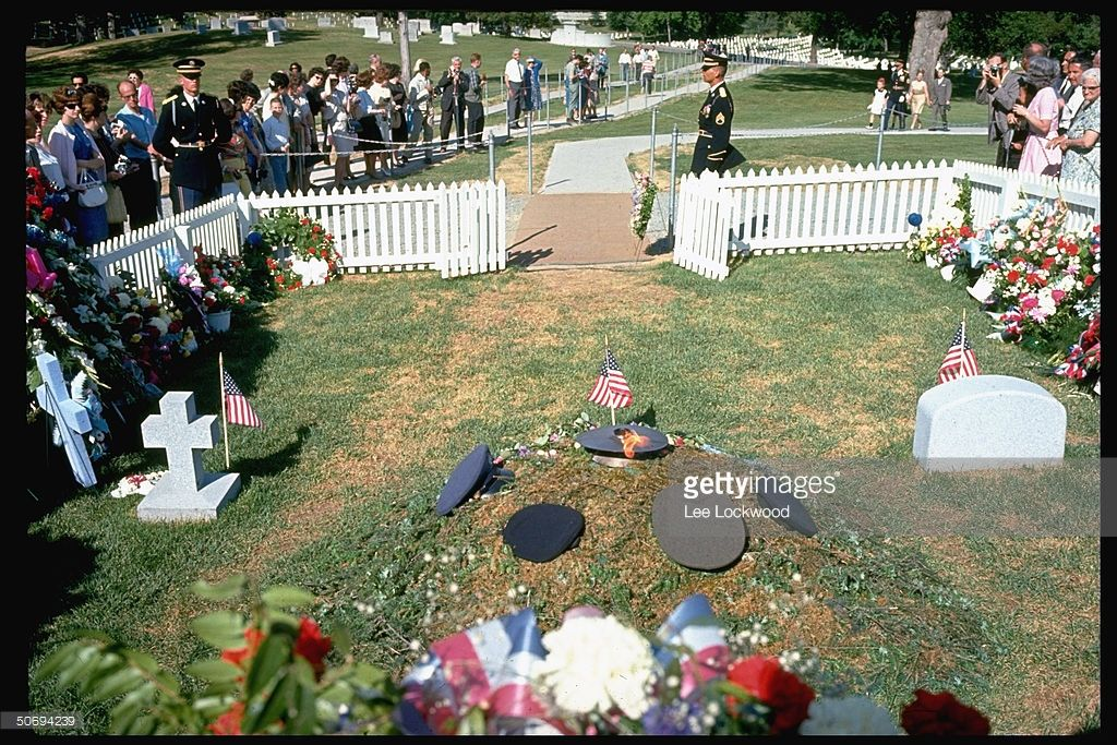 News Photo : Visitors at grave site paying respects to slain...