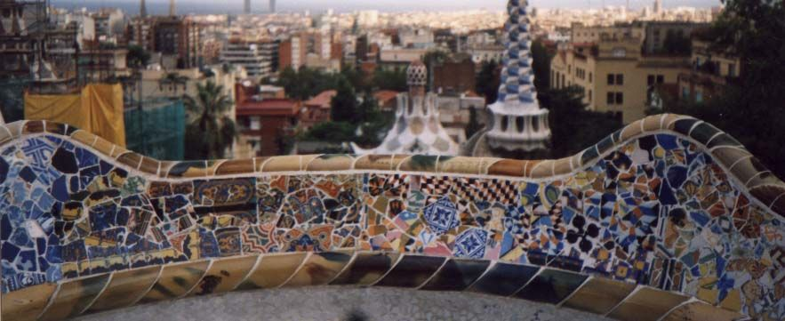 The bench at the Guell Park snakes its way around the edge of a large open-air square. The park was originally designed as an idealistic housing complex, and was built between 1900 and 1914. Construction of the bench was in the later stages (1910 to 1913). Gaudì is said to have used seated workmen as actual models for the form of the seat. Jujol carried out the decoration, using tiles as trencadis, with handmade ceramics, including hand-painted discs. He added colour and graffiti (such as…