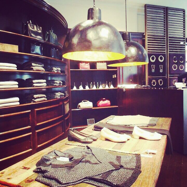 I like the use of large lighting over the table displaying products in Adolf Dominguez Barcelona August 2014