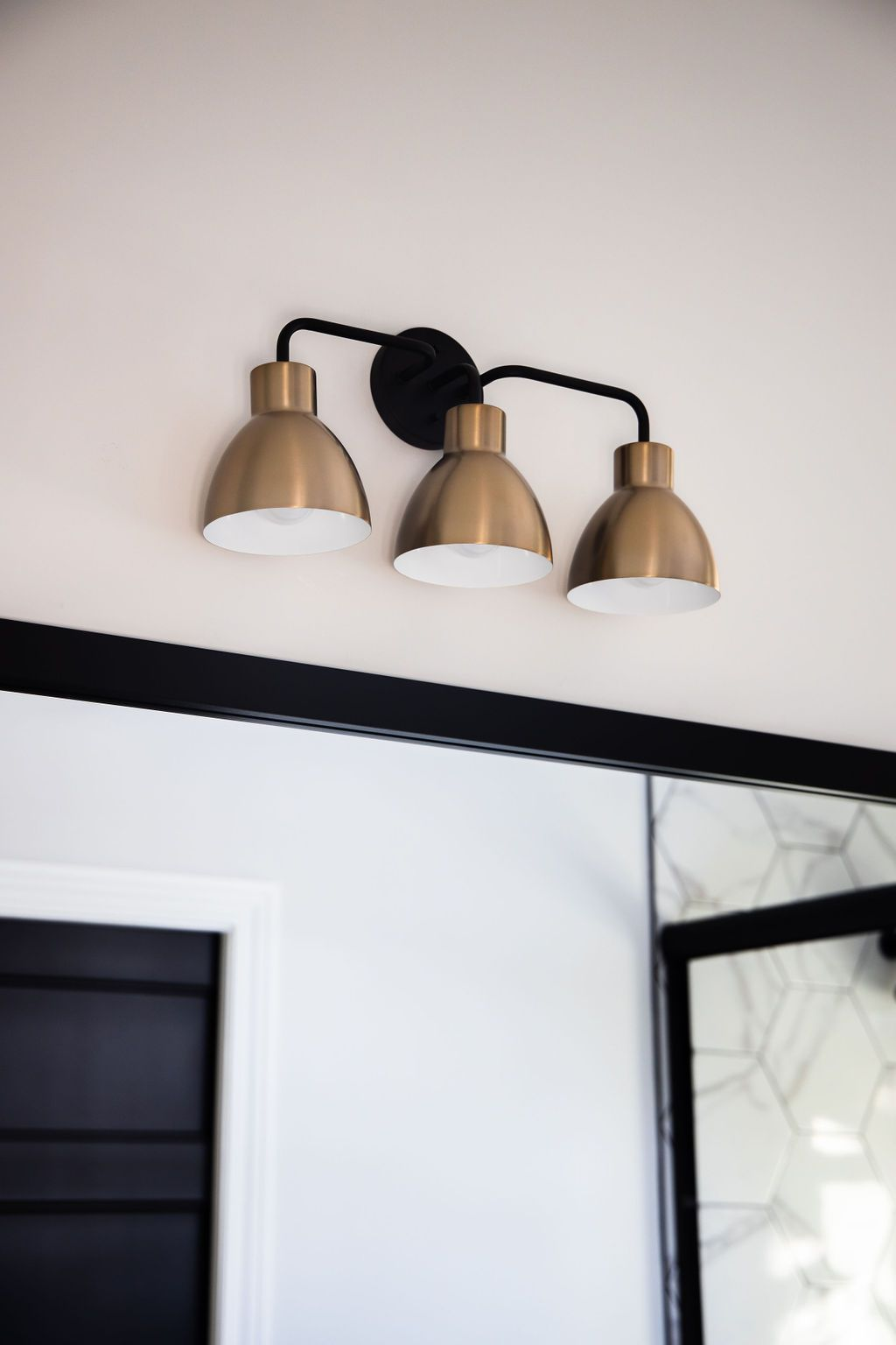 Photo of Black and brass bathroom lighting