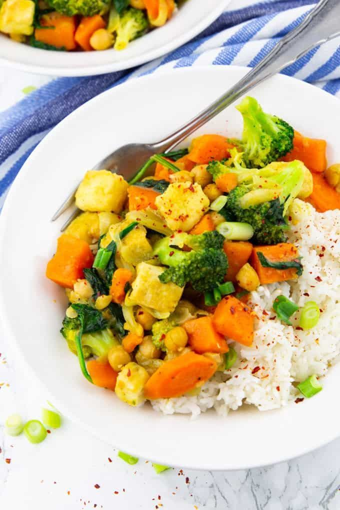 Gemüsecurry mit Basmatireis auf weissem Teller mit Gabel auf Marmor ...   - Curry und Dal Rezepte | REISHUNGER -