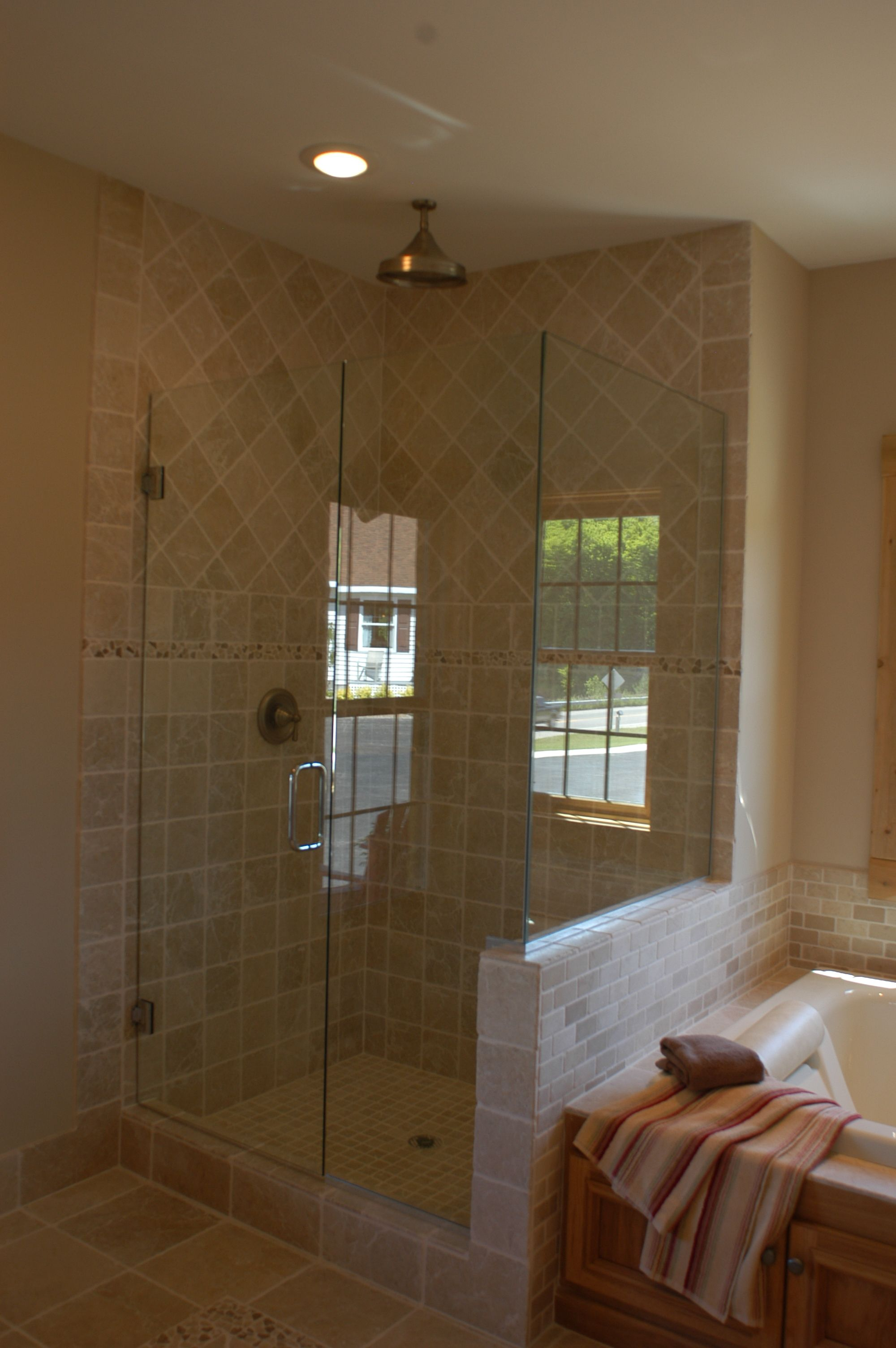 glass enclosed tile shower with a rain forest shower head ...
